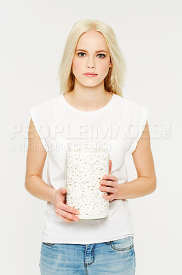 Buy stock photo A beautiful young woman holding a jar of pills against a white background