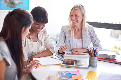 Buy stock photo Cropped shot of three businesswoman gathered around a table in the office