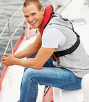 Happy young guy wearing a life jacket sitting in a sailboat at sea