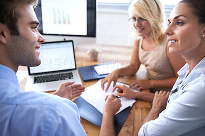 Buy stock photo Three young executives sitting around a table discussing paperwork
