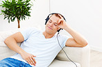 Cute young man listening to music in the comfort of his home