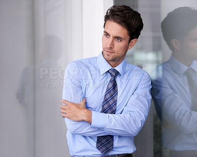 Buy stock photo Shot of a young businessman looking deep in thought
