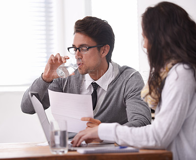 Buy stock photo A young man drinking water during an interview