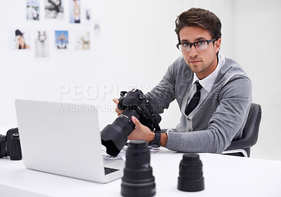 Buy stock photo Portrait of a photographer sitting at a desk in his office holding a camera