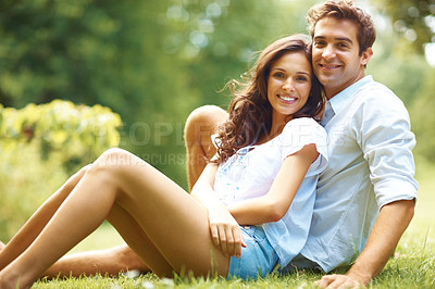 Buy stock photo Shot of an affectionate young couple relaxing in the park
