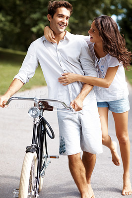Buy stock photo Shot of an affectionate young couple cycling in the park