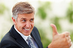 Closeup of a senior handsome business man with his thumb up