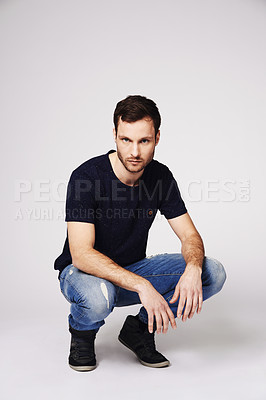 Buy stock photo Portrait of a handsome young man crouching in studio