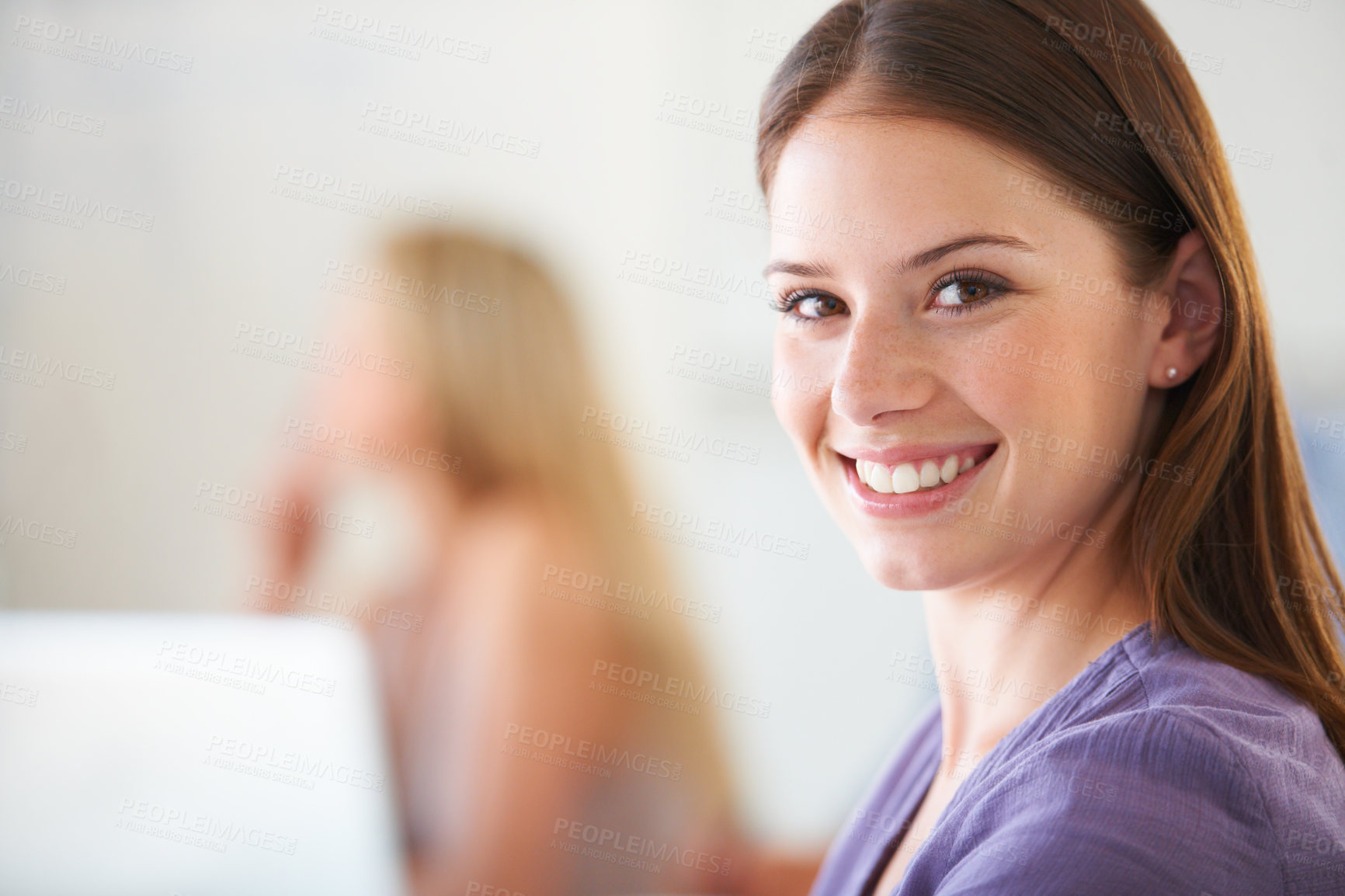 Buy stock photo A casual young businesswoman smiling with a blurred colleague in the background