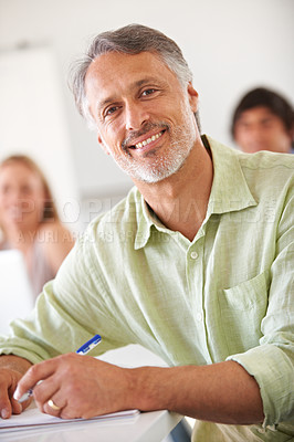 Buy stock photo Smiling mature businessman taking some notes while looking at the camera
