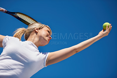 Buy stock photo A young tennis player serving during a match