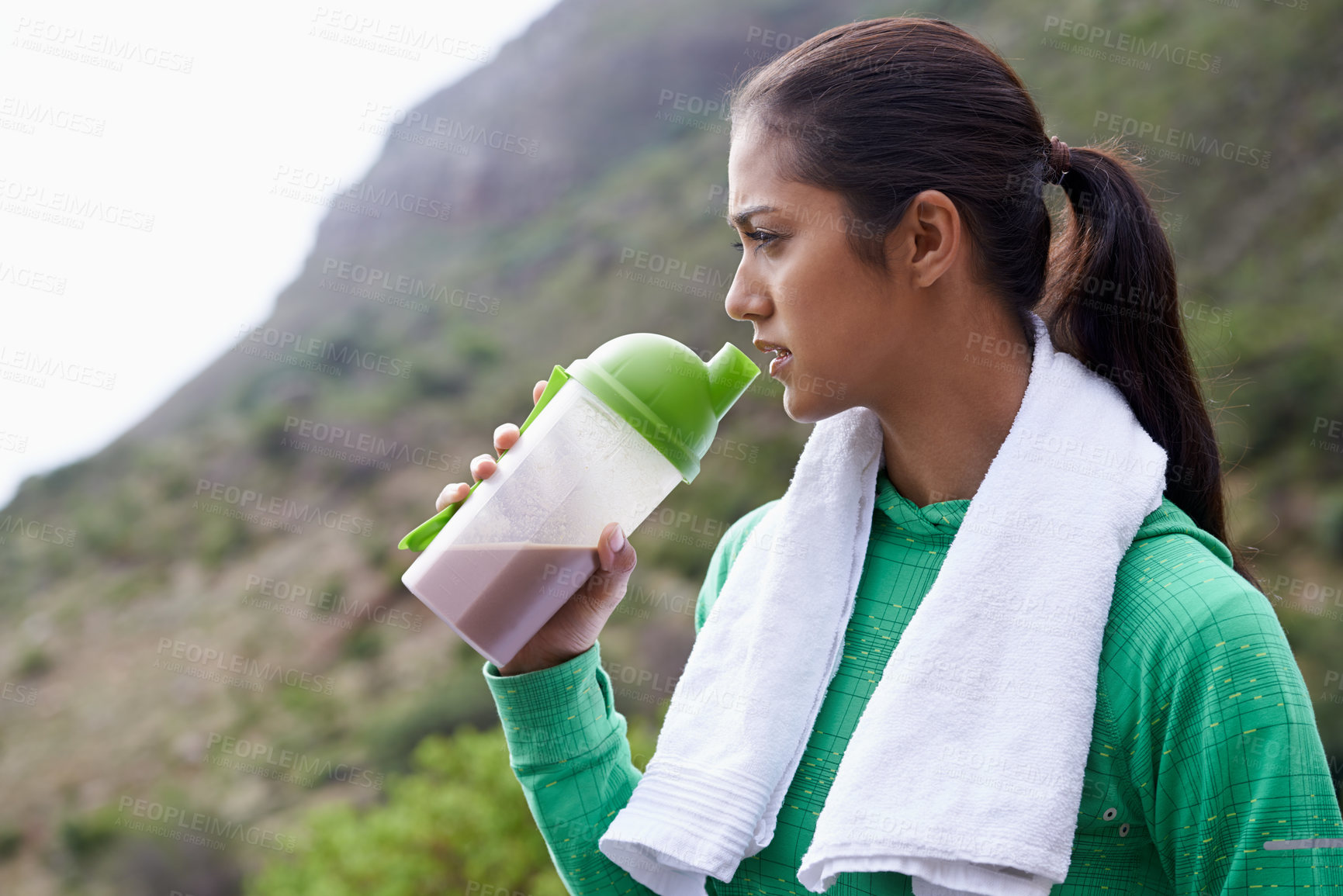 Buy stock photo A young ethnic woman drinking a sports drink outdoors