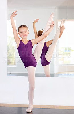 Buy stock photo A young ballerina lifting her leg in front of a mirror