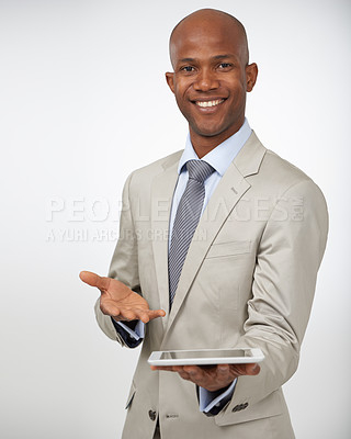 Buy stock photo Attractive young man holding his tablet and smiling