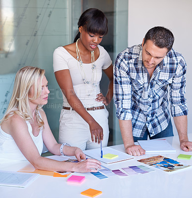 Buy stock photo Three colleagues choosing a colour scheme in the boardroom