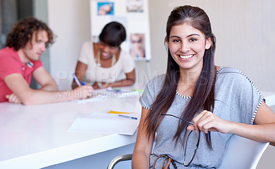 Buy stock photo A young businesswoman sitting at her desk while smiling at the camera