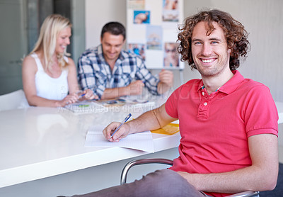Buy stock photo A young man with curly hair sitting in the boardroom with his peers