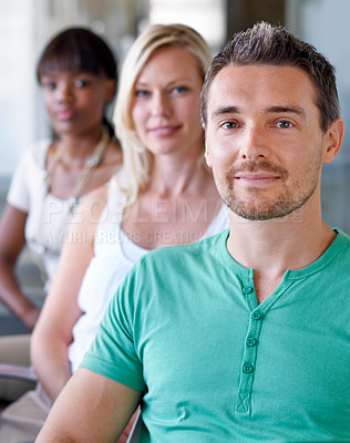 Buy stock photo Three creative professionals sitting in a line in their boardroom together