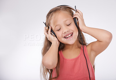 Buy stock photo Studio shot of a little girl singing along to music playing over her headphones