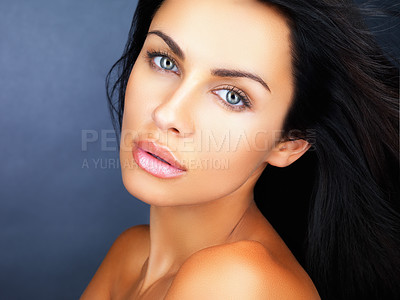 Buy stock photo Closeup of an alluring woman with radiant skin and rich dark hair, isolated on blue background