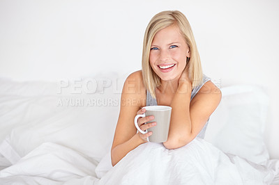 Buy stock photo An attractive young woman drinking coffee while sitting in bed