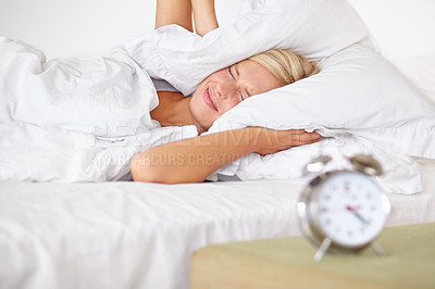 Buy stock photo An attractive young woman covering her ears to block her alarm clock