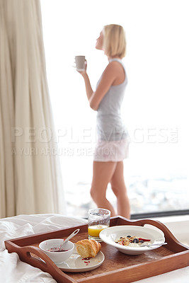 Buy stock photo A young woman drinking coffee and looking out of her window on a bright morning