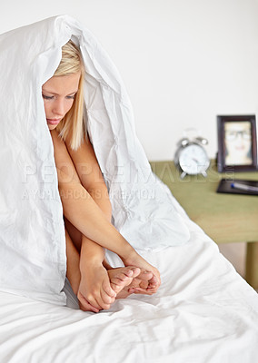 Buy stock photo Shotof a young blonde woman sitting under her covers with her bedside table and alarm clock in the background