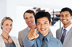 Asian business man pointing at you with colleagues in background