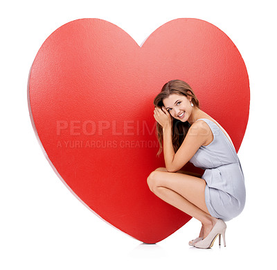 Buy stock photo Portrait of an attractive young woman crouching in front of a giant heart-shaped prop