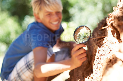 Buy stock photo A boy looking through a magnifying glass