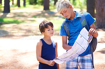Buy stock photo Two boys inspecting a map while hiking in the forest