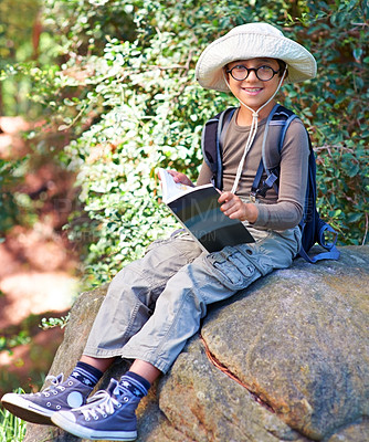 Buy stock photo Shot of a little boy with a book in his hand sitting on a rock