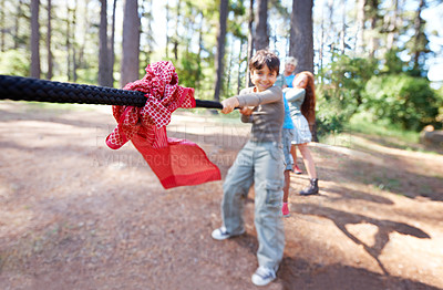 Buy stock photo View of a group of happy children playing tug of war outdoors
