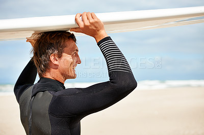 Buy stock photo Shot of a smiling young surfer at the beach carrying his board on his head