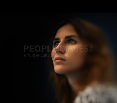 Buy stock photo A gorgeous young woman looking away against a dark background