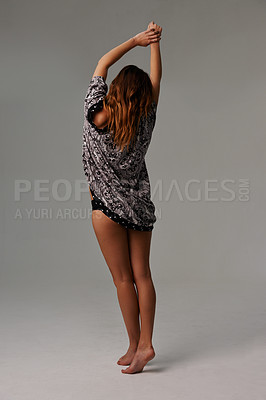 Buy stock photo Rear view of a young woman in lingerie stretching her arms