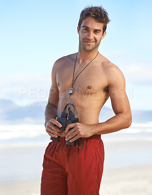 Buy stock photo Portrait of a handsome young lifeguard holding binoculars at the beach