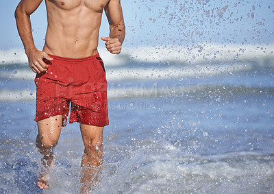 Buy stock photo Cropped shot of a male lifeguard running through the water