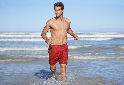 Buy stock photo A handsome young lifeguard running through the waves