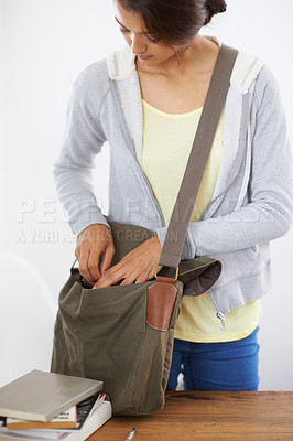Buy stock photo Cropped shot of young student packing books into her bag