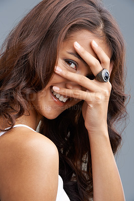 Buy stock photo A playful woman smiling at the camera with her hand over her face