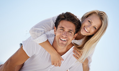Buy stock photo A handsome young man giving his girlfriend a piggyback ride outside