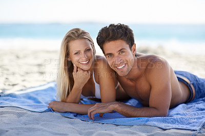Buy stock photo A young couple spending a relaxing day on the beach together