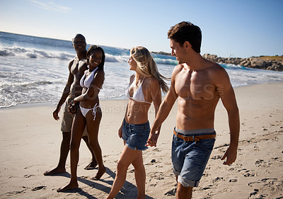 Buy stock photo Two young couples taking a walk on the beach together