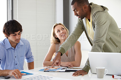 Buy stock photo Three talented coworkers brainstorming a project together in the boardroom
