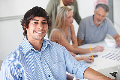 Buy stock photo A group of designers sitting around a boardroom table having a discussion while one smiles at the camera