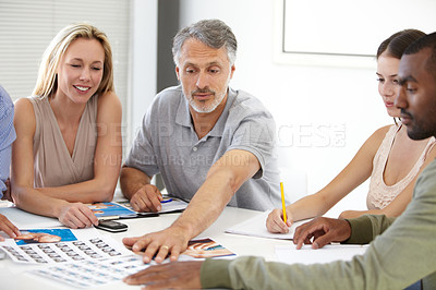 Buy stock photo A mature man pointing something out to his colleagues in a boardroom meeting