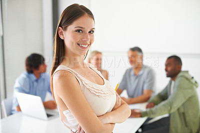 Buy stock photo A gorgeous brunette crossing her arms while standing in front of her colleagues in the boardroom