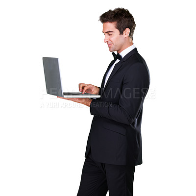 Buy stock photo A young businessman standing while typing on a laptop